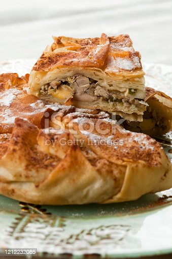 Delicious homemade chicken Moroccan pastilla (pastela) slices, ready to eat. Close-up traditional flavors and pies ingredients. Foods, Moroccan cuisine, borek or burek, pastries, recipes, culinary culture concept. Vertical.