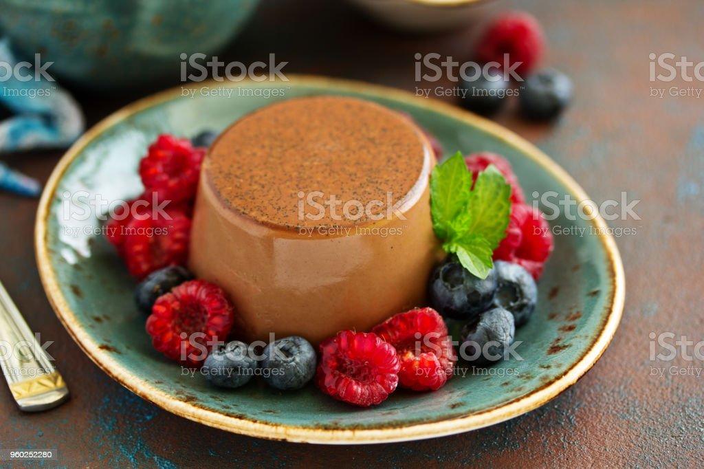 Delicious home-made chocolate dessert Panna cotta. Cream-caramel, caramel custard, with raspberries and blueberries. stock photo