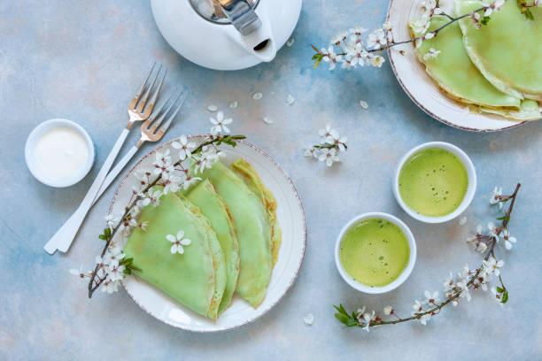 Deliciosas panquecas verdes caseiras com galhos de cerejeira florescendo com chá verde de matcha no fundo azul celeste. Vista superior, feche acima - foto de acervo