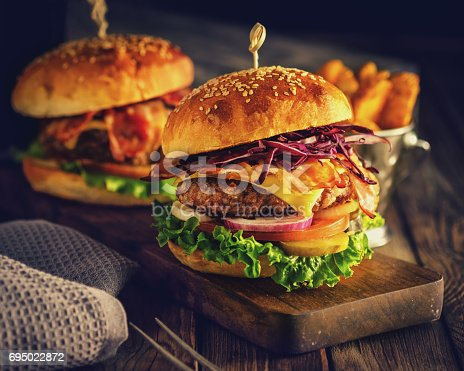 istock Delicious homemade hamburger on wooden background 695022872