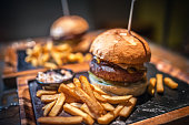 Delicious homemade hamburger with french fries on wooden background