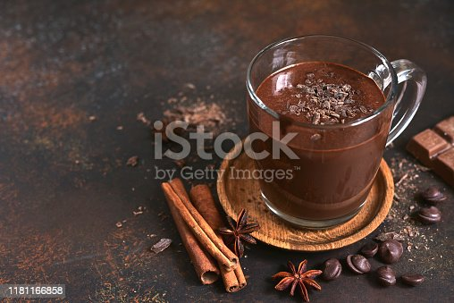 Delicious homemade hot chocolate with cinnamon in a glass cup on a dark slate, stone or concrete background.