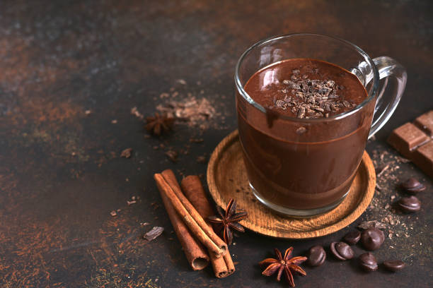 Delicious homemade hot chocolate with cinnamon Delicious homemade hot chocolate with cinnamon in a glass cup on a dark slate, stone or concrete background. theobroma stock pictures, royalty-free photos & images