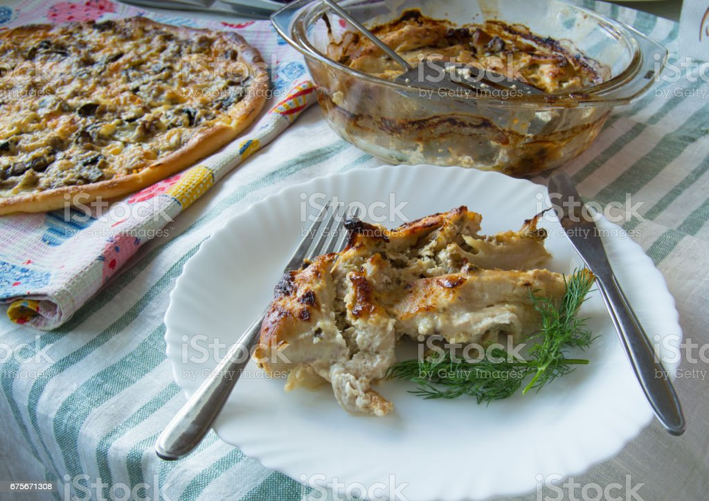 A delicious homemade lunch - pizza, baked chicken breast on a white plate royalty-free stock photo
