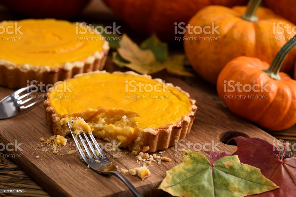 Delicious homemade open pumpkin pies being eaten with forks on rustic wooden board served with orange pumpkins and marple leaves stock photo