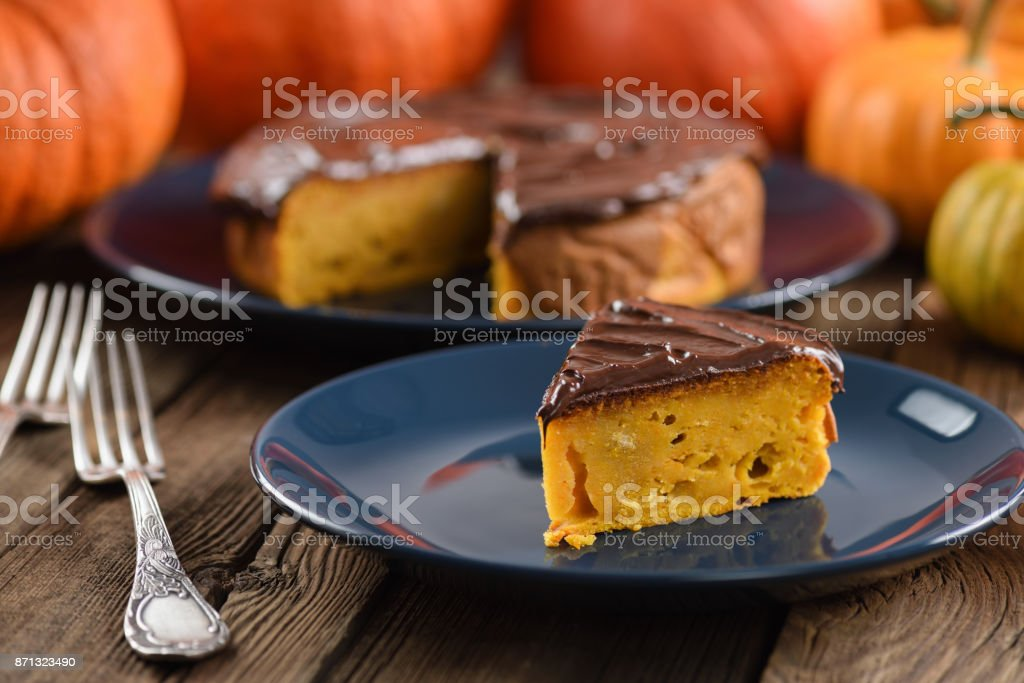 Delicious homemade pumpkin cake with chocolate icing served on dark blue plates with bright orange pumpkins stock photo