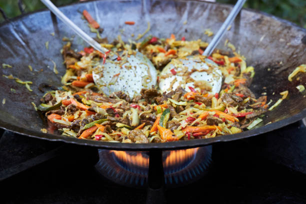 Delicious homemade wok is cooked in a large frying pan on a gas stove stock photo