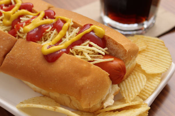delicious hot dog with ketchup, mustard and chips - hot dog stock pictures, royalty-free photos & images