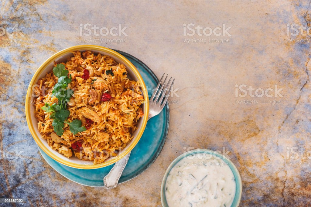 Delicious Indian biryani with cucumber raita side dish stock photo