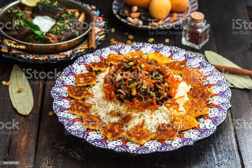Delicious Iranian jewelled rice topped with nuts, raisins and orange zest stock photo