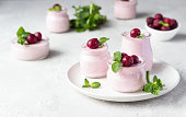Delicious Italian dessert cherry panna cotta with fresh cherries and mint in jars. Light grey stone background, selective focus. Copy space.