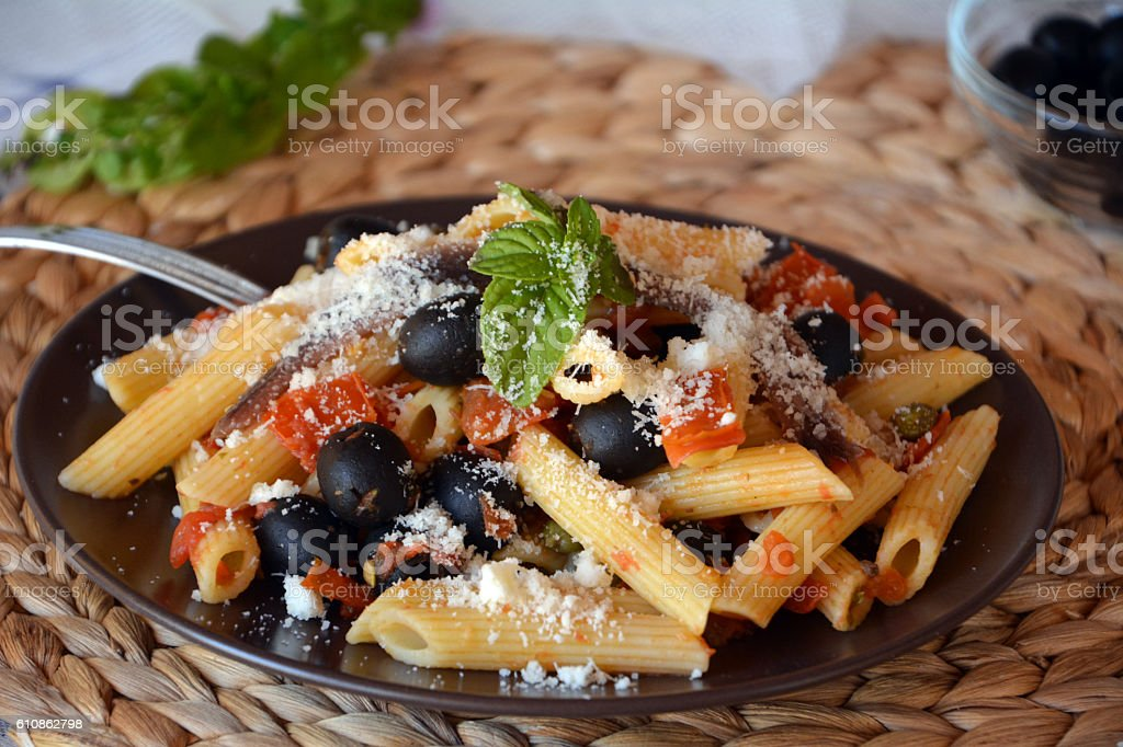 Delicious italian pasta penne with anchovies on a plate. stock photo