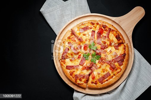 istock Delicious Italian pizza sliced ham, bacon and cheese with food ingredients on old kitchen table. 1005391222