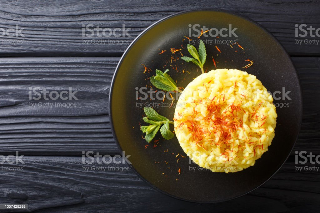 Delicious Italian risotto with saffron and mint (Risotto alla milanese) closeup. horizontal top view from above stock photo