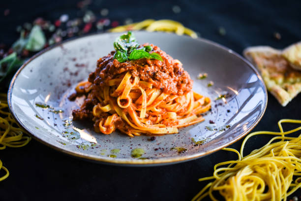 delicious italian spaghetti bolognese with minced beef sauce, tomatoes, carrots & fresh basil delicious italian spaghetti bolognese with minced beef sauce, tomatoes, carrots & fresh basil bolognese sauce stock pictures, royalty-free photos & images