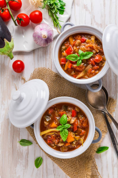 Delicious Italian vegetable minestrone soup served in small pots with ingredients stock photo