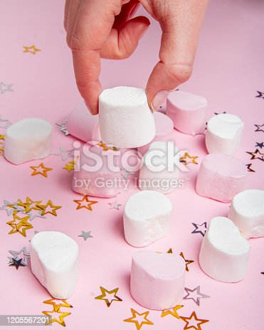 Very pretty candies for children. Marshmallow on the pink background with small stars. Photography for party