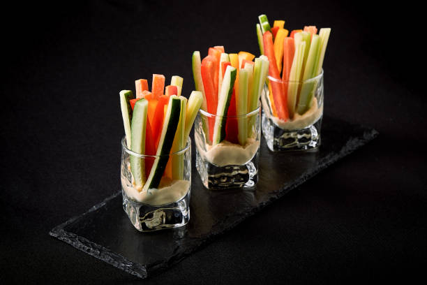 Delicious juicy cucumbers, carrots, celery, cut into thin strips or clubs, are served in a glass glass as snacks to plunge into a spicy sauce. Fusion food concept, low key, copy space stock photo