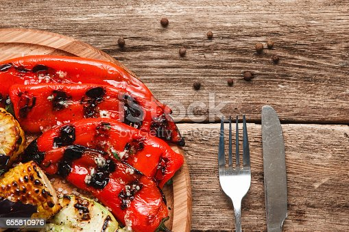 655793486 istock photo Delicious juicy grilled vegetables on wood platter 655810976
