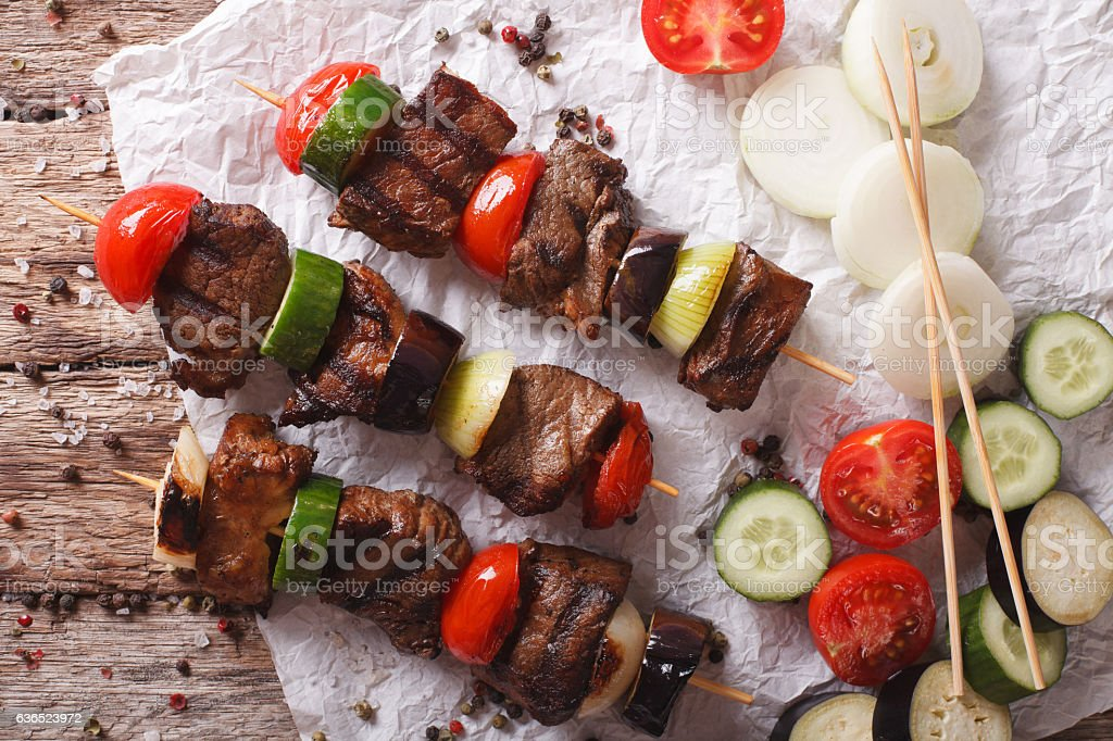 Delicious kebab with vegetables on skewers close-up. horizontal stock photo
