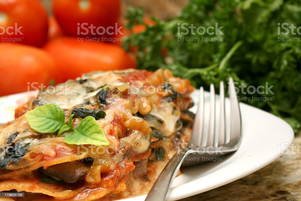 Delicious lasagna served on a white plate with garnish  stock photo