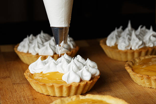 Delicious lemon curd tartlets  with meringue on wooden  table A process of decorating lemon tartlets with meringue icing icing bag stock pictures, royalty-free photos & images