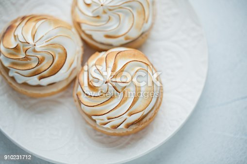 Delicious lemon tartlets with meringue on a white vintage plate. Sweet treat on a light blue background.