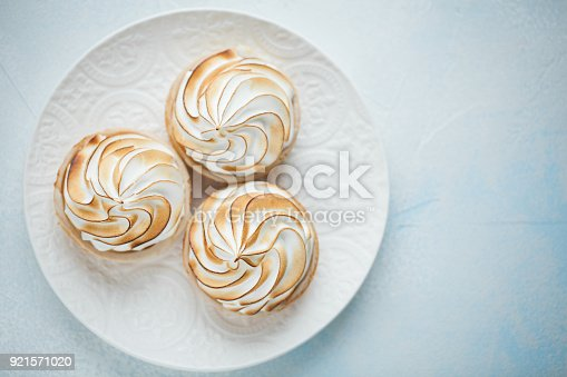 Delicious lemon tartlets with meringue on a white vintage plate. Sweet treat on a light blue background. Flat lay and copy space. Top view.
