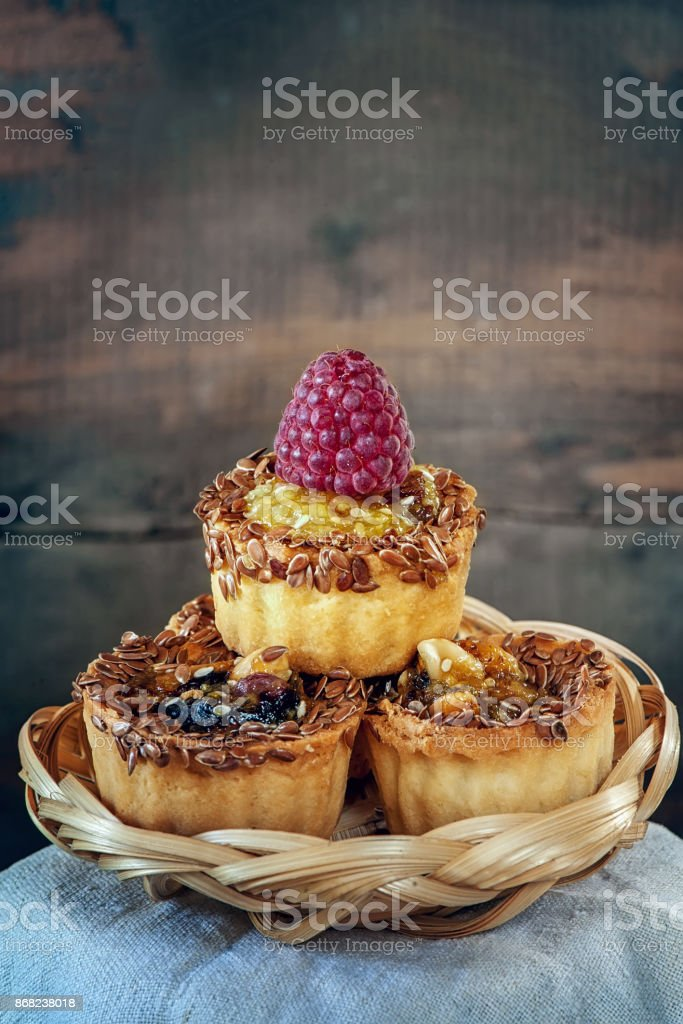 Delicious little pumpkin muffins, decorated with caramel, flax and raspberries. Copy space. stock photo