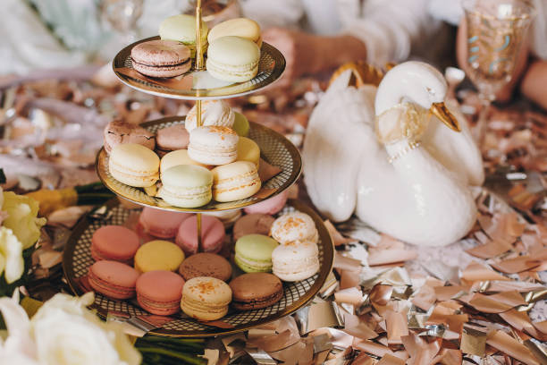 leckere makronen auf schönen jahrgang messestand und champagner-gläser auf tisch mit gold und silber konfetti und ente. luxus catering. brautmoden henne oder baby-dusche. festliche feier - tischdeko goldene hochzeit stock-fotos und bilder