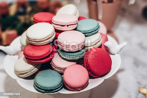 delicious macaroons. candy bar at luxury wedding reception. exclusive expensive catering. table with modern desserts. space for text. baby or bridal shower. holiday celebration