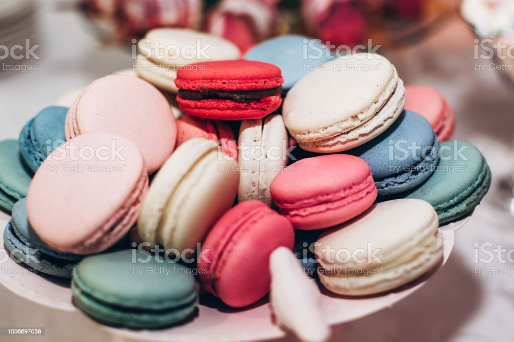 delicious macaroons close-up. candy bar at luxury wedding reception. exclusive expensive catering. table with modern desserts. space for text. baby or bridal shower. holiday celebration stock photo
