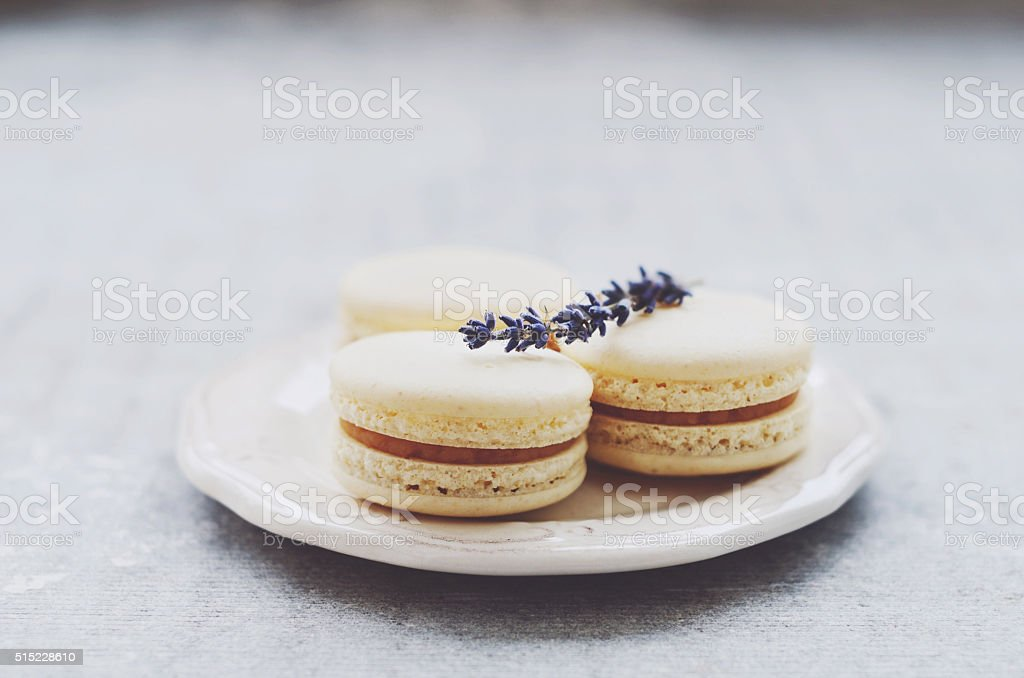 Delicious macaroons decorated with lavender on white china plate stock photo