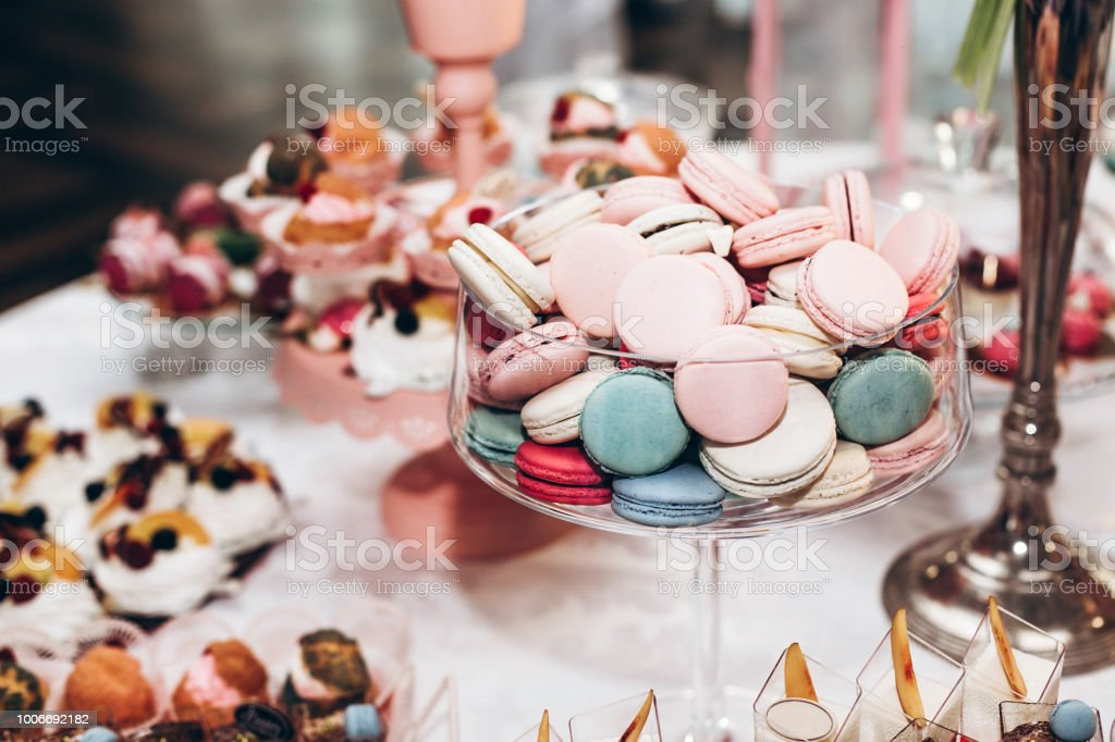 delicious macaroons in glass bowl. candy bar at luxury wedding reception. exclusive expensive catering. table with modern desserts. space for text. baby or bridal shower. holiday celebration stock photo