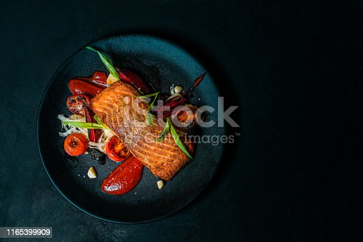 Delicious meal on a black plate, top view, copy space.