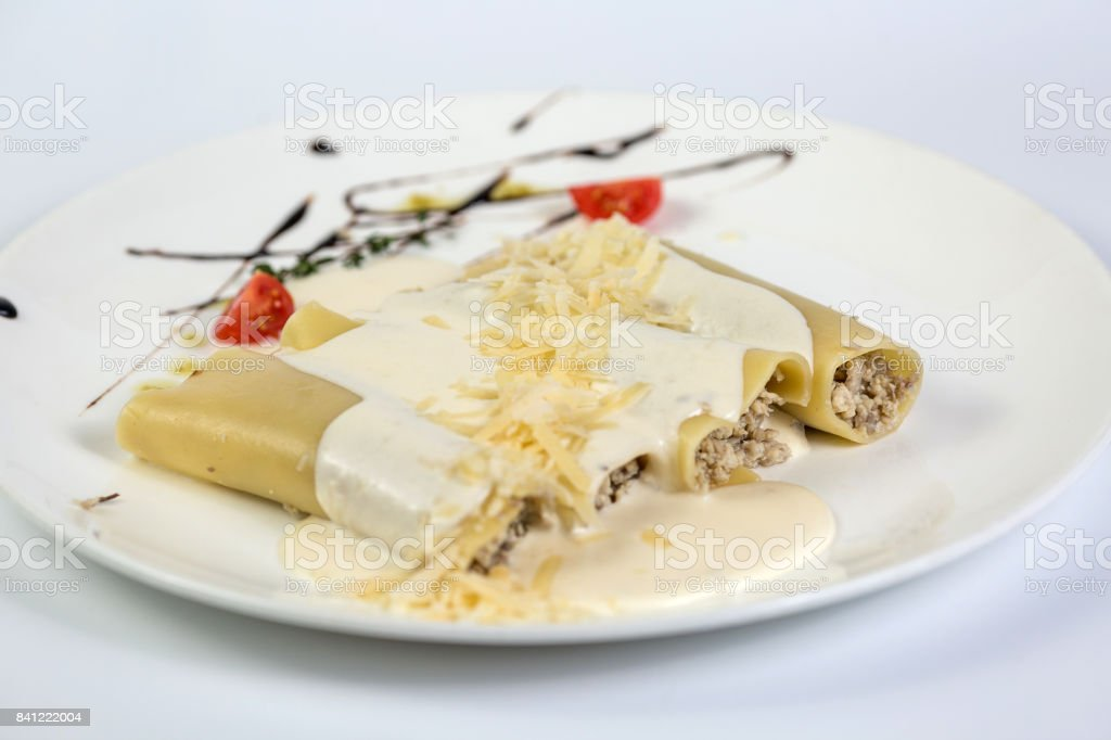 Delicious meat filled pasta on a plate on white background. Italian cannelloni, Spanish canelones. stock photo