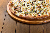 istock Delicious meat pizza on wooden board. Made with Mozzarella, picanha meat, onion, cheese, tomato sauce. Filet Steak, meat. Horizontal photograph top alignment. 1240626151