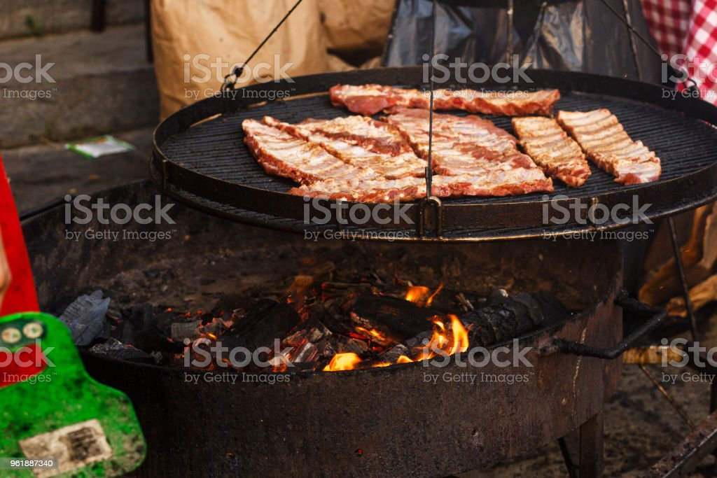 delicious meat ribs grilling on open grill, outdoor kitchen. food...