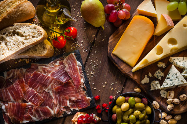Delicious Mediterranean appetizer shot from above Typical Mediterranean food concepts: Top view of a rustic wooden table filled with delicious Mediterranean appetizer. The composition includes a cheese selection, Iberico ham slices, pears, cherry tomatoes, pomegranate, pickles, olive oil, grapes, olives, pistachio and bread. Predominant color is brown. Low key DSRL studio photo taken with Canon EOS 5D Mk II and Canon EF 100mm f/2.8L Macro IS USM. olive fruit stock pictures, royalty-free photos & images