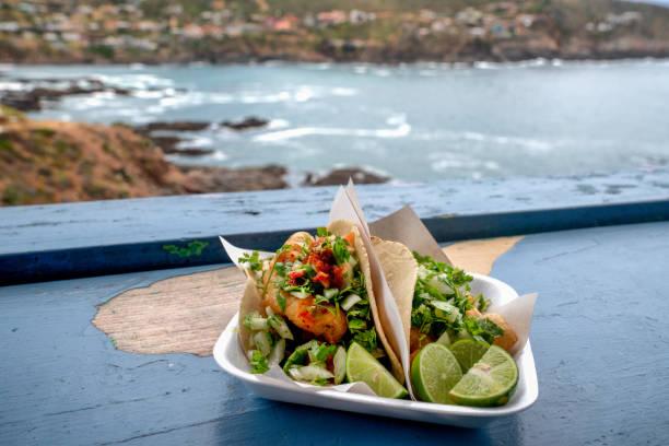 köstliche mexikanische shrimp tacos in einem beach outdoor restaurant - meeresfrüchte enchiladas stock-fotos und bilder