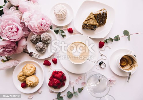 istock Delicious morning breakfast table essentials: fresh cappuccino coffee, marshmallow, cookies, chocolate, red raspberries, glass of water and tender pink blossoming peony bouquet on the white background 1047503218
