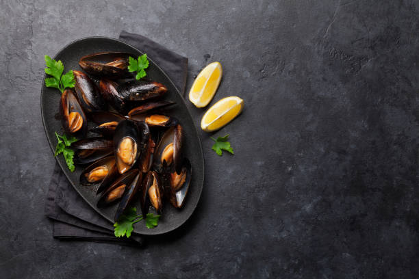 Delicious mussels with tomato sauce and parsley Delicious cooked seafood mussels with tomato sauce, parsley and lemon. Top view with space for your text. mussel stock pictures, royalty-free photos & images