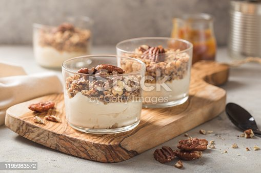 Delicious natural yogurt parfait with caramel, pecan nuts on conctere background