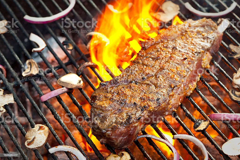 Delicious New York Strip Steak on a Flaming Charcoal Grill royalty-free stock photo