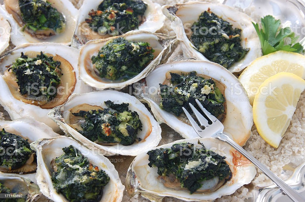 A delicious Oysters Rockefeller with fork and lemon stock photo