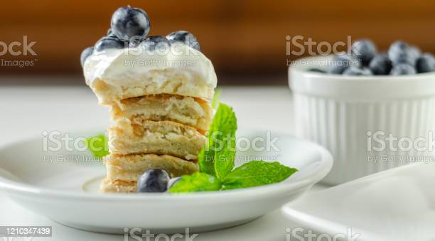 Photo of Delicious pancakes with sweet creamy yogurt and fresh berries with mint,