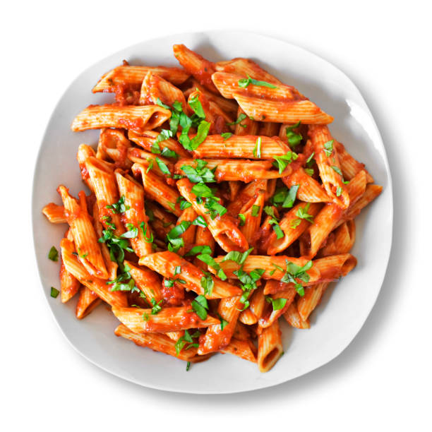 Delicious pasta dish with fresh basil on white Delicious pasta dish with fresh basil on white background. Top view scene, healthy eating or healthy lifestyle. Penne napoli or pasta arrabiata, isolated. rigatoni stock pictures, royalty-free photos & images