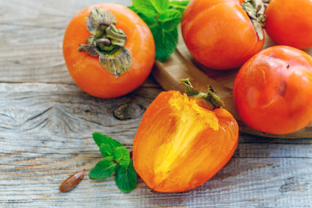 delicious persimmon fruit and mint. - diospiro imagens e fotografias de stock