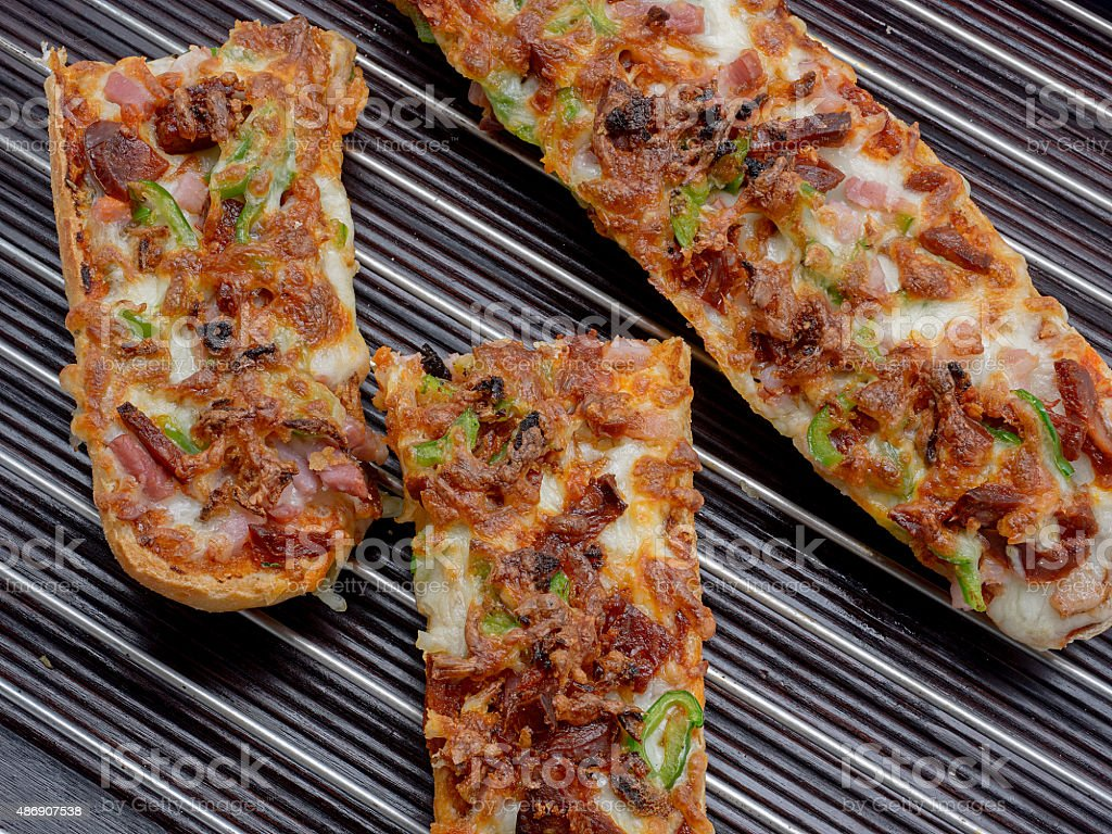 Delicious pizza baguette with mozzarella, green pepper, onion, t stock photo