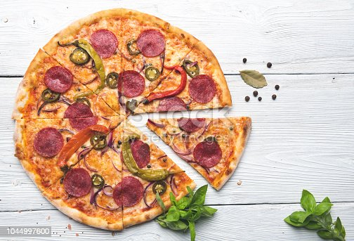 Whole pizza on white wooden table. Top View